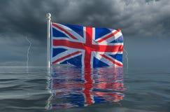 Union Jack or Union Flag sinking under waves wiht hard brexit. Brexit image of UK flag Union Jack sinking slowly under the waves in storm royalty free stock photo
