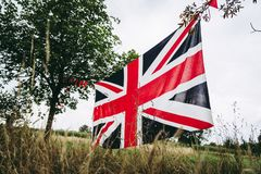Union Jack flag stretched between trees. England in the forest stock photos