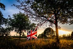 Union Jack flag stretched between trees. England in the forest stock photography