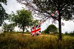 Union Jack flag stretched between trees. England in the forest royalty free stock photography