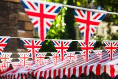 Strings of Union Jack bunts festive decoration in London England. Union Jack flag triangular bunting hanging in a street, a festive decorations in London England Royalty Free Stock Photography
