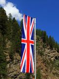 Union Jack, flag of the United Kingdom against forest and blue sky background stock photo