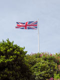 Union Jack flaga lata nad niebieskiego nieba tłem zdjęcie stock