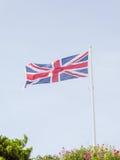 Union Jack flaga lata nad niebieskiego nieba tłem Obraz Royalty Free