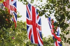 Union Jack flagga som vinkar ovanför Bruton Street i London royaltyfri foto