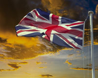 Union Jack on flagpole under dark brooding sky. Union Jack flying on flagpole with dark brooding sky at sunset.  Concept image indicating stormy times ahead for Royalty Free Stock Images
