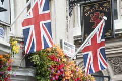 2 Union Jack flags and a pub sign in London. 2 Union Jack flags and a pub sign are seen near Westminster in London on 9/18/17 Royalty Free Stock Photos