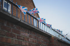 Union jack flags. Small union jack flags on a balcony in windy cold weather. typical british red brick building in the background Stock Image