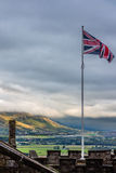 Union Jack flying over Stirling landscape. Union Jack flying  against a steely gray background over Stirling Castle in Scotland. Dark skies contrast with sun Stock Photo