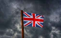 Union Jack in front of gathering storm clouds royalty free stock photography