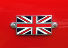 Union Jack metal badge. Detail on a vintage red sports car royalty free stock photos