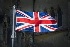Union Jack na luz solar contra o fundo da catedral Imagens de Stock Royalty Free