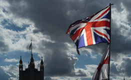 Union Jack and Parliament. The Union Jack and flag of St George fly over a souvenir stall on Westminster Bridge. The houses of Parliament in the background Stock Image