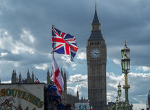 Union Jack and Parliament. The Union Jack and flag of St George fly over a souvenir stall on Westminster Bridge. The houses of Parliament in the background Stock Photography