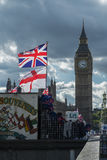 Union Jack and Parliament. The Union Jack and flag of St George fly over a souvenir stall on Westminster Bridge. The houses of Parliament in the background Royalty Free Stock Images