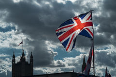 Union Jack and Parliament. The Union Jack and flag of St George fly over a souvenir stall on Westminster Bridge. The houses of Parliament in the background Royalty Free Stock Photo
