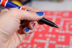 Union Jack pen and nail polish. Blue nails Royalty Free Stock Photography