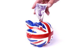 Union jack pippy bank with money. English money with a union jack piggy bank on white background with twenty pound note stock photography