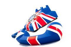 Union Jack telephone with the receiver off the hook laying in front of the phone isolated on the white background. Union Jack telephone with pattern of British Stock Image