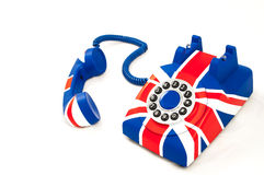 Union Jack telephone with the receiver off the hook laying in front of the phone isolated on the white background. Union Jack telephone with pattern of British Royalty Free Stock Photography