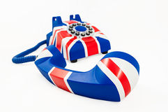 Union Jack telephone with the receiver off the hook laying in front of the phone isolated on the white background. Union Jack telephone with pattern of British Royalty Free Stock Images