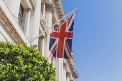 Union Jack-vlag die van een elegant historisch gebouw in Lo golven Stock Foto's
