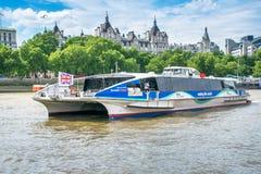 Union Jack vuela en el autobús del río de Londres mientras que pasa a Somerset House Imagenes de archivo