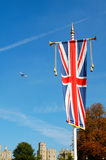 Union jack at Windsor Castle, London. A union jack banner at Windsor Castle, London with a plane flying overhead Royalty Free Stock Images