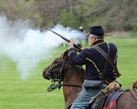 Union Soldier Firing Gun - Civil War Reenactment. Union soldier firing shots during civil war reenactment Stock Photos