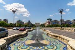 Union Square springbrunn och hus av folk- eller parlamentslotten i Bucharest Arkivfoto