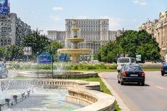 Union Square springbrunn och hus av folk- eller parlamentslotten i Bucharest Royaltyfria Foton