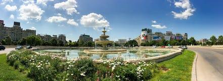 Union Square springbrunn och hus av folk- eller parlamentslotten i Bucharest Arkivbilder