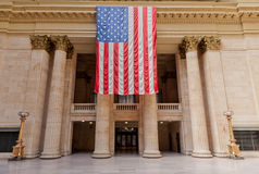 Union Station in Chicago. The main hall of Union Station with a large flag of USA hanging in front of the corinthian columns Royalty Free Stock Photo