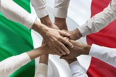 Union or Team Hands multcultural people team over italian flag topview.  stock photos