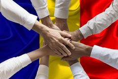 Union or Team Hands multcultural people team over romanian flag topview.  royalty free stock images