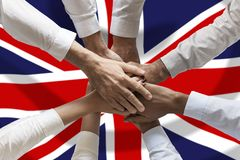 Union or Team Hands multcultural people team over United Kingdom flag topview.  royalty free stock photography