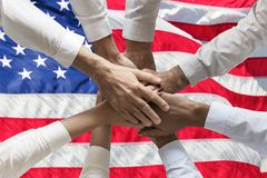 Union or Team Hands multcultural people team over usa or us or Americanflag topview.  stock photo