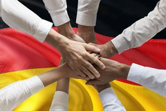 Union or Team Hands multcultural people team over german flag topview.  stock images