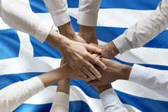 Union or Team Hands multcultural people team over greek flag topview.  stock photo