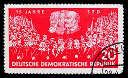 Union of two demonstrations, portraits of Marx, Engels and Lenin, 15 years Socialist Unity Party of Germany (SED) serie, circa. MOSCOW, RUSSIA - SEPTEMBER 15 stock illustration