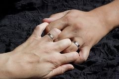 Union with you my love. Two white hands holding wedding rings are held by the fingers on a dark cloth Royalty Free Stock Image