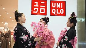 Uniqlo geisha. Moscow, Russia - March 5, 2017: Three geisha in traditional Japanese kimono with sakura branches at the entrance to the uniqlo store. Performance stock video