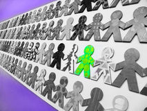 Unique. Conceptual photograph image for being unique and special - of a single green person standing out in a crowd of other black and white people.  Simple Royalty Free Stock Image