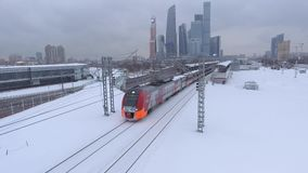 Modern train near Moscow city Russian skyscrapers. Lastochka second metro ring. Subway intersection. Highway. Unique aerial drone 4K footage. Winter day snow stock footage