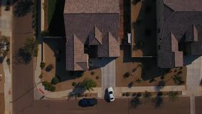 Aerial View of Car Pulling Out of Residential Driveway. 7885 A unique aerial view of a car pulling out of a typical Arizona neighborhood residence. Phoenix stock video footage