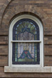 Unique arched stained glass window. Arched stain glass window on brick wall Stock Photo