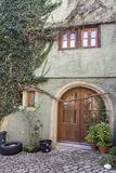 Unique beautiful home entrance with round wooden door and vine climbing on the house wall. In germany Royalty Free Stock Photo