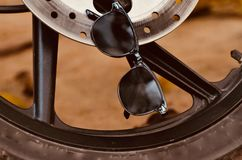 A black sunglass with a tyre background photograph. The unique black coloured sunglass hanging with a motor bike tyre object stock photograph Stock Image