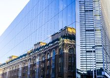 Victorian house reflection in a modern glass building in the big city stock images