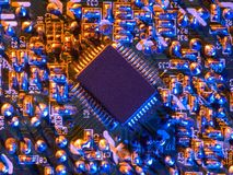 Unique Chip. A unique chip on an electronic circuit board with many soldered connections Royalty Free Stock Image